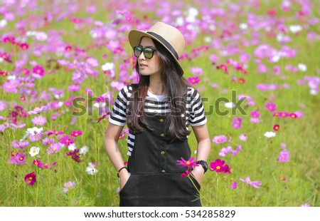 Portrait of Cosmos flower field with beautiful girl wear hat and sunglass in dress black chill day have a holiday