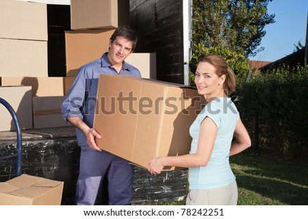 Portrait of couple carrying cardboard box while moving into new home - stock photo