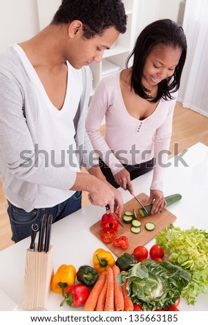 Portrait Of Couple Chopping Vegetables In Kitchen - stock photo