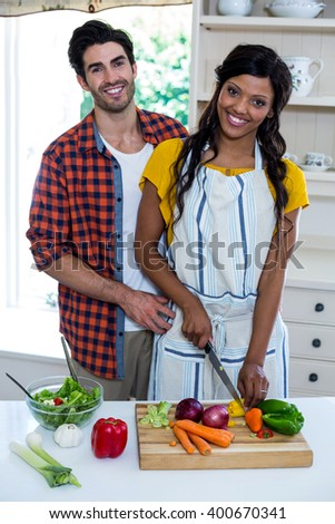 Portrait of couple chopping vegetables in kitchen at home