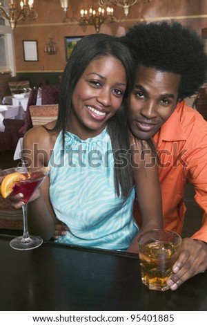 Portrait of couple drinking at bar - stock photo