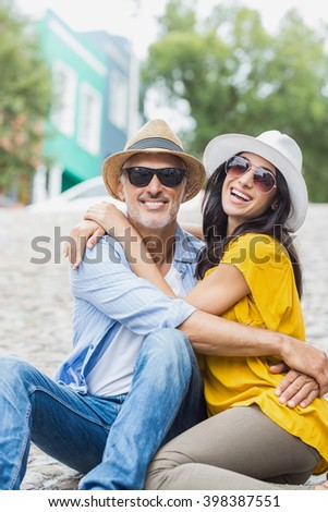 Portrait of couple embracing while sitting outdoors - stock photo