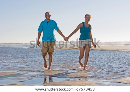 Portrait of couple holding hands at beach - stock photo