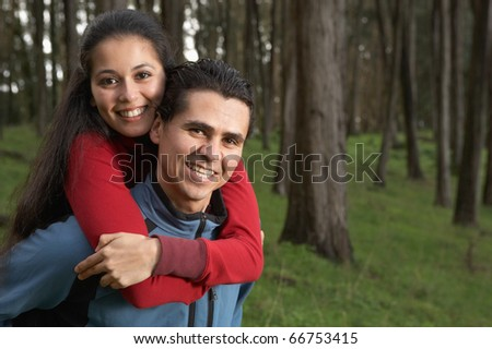 Portrait of couple hugging in forest - stock photo