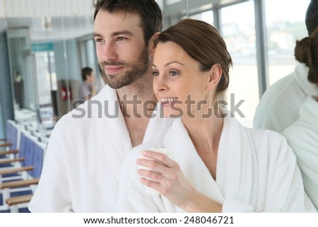 Portrait of couple in bathrobe spa center relaxation room - stock photo