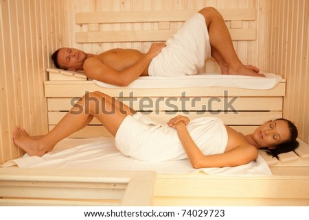 Portrait of couple in sauna, lying on towels with eyes closed, relaxing.? - stock photo