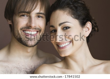 Portrait of couple in studio, smiling - stock photo