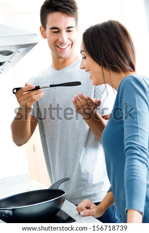 Portrait of couple in the kitchen preparing breakfast - stock photo