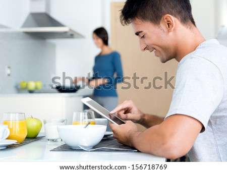 Portrait of couple in the kitchen preparing breakfast and browsing  internet  with a digital tablet - stock photo