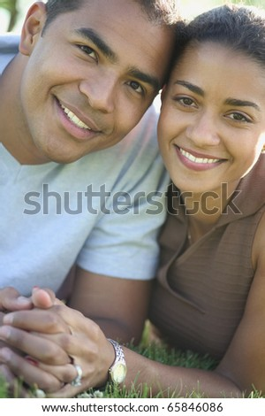Portrait of couple laying in grass - stock photo