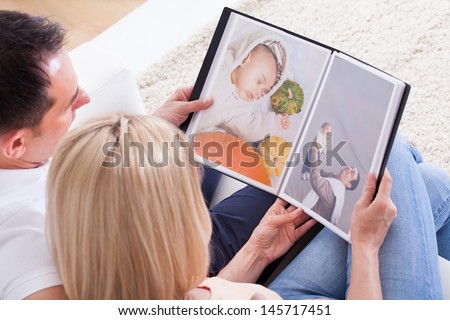 Portrait Of Couple Looking At Photo Album