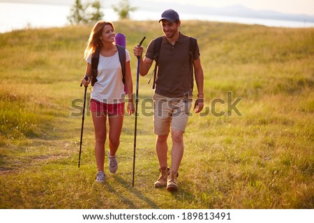 Portrait of couple of happy hikers walking in the countryside