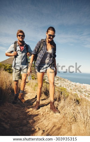 Portrait of couple of happy hikers walking in the countryside. Young caucasian man and woman hiking on a summer day. - stock photo