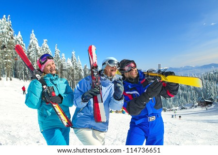 Portrait of couple of skiers standing on ski slope - stock photo
