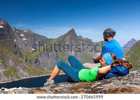 Portrait of couple of trekkers on top of mountains in Norway - stock photo