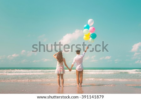 Portrait of couple of young happy married hipsters in trendy vintage clothes standing together on the beach with balloons. Sunny summer day. Pastel colors tone  - stock photo