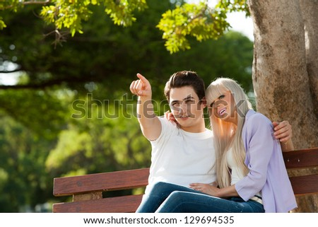 Portrait of couple on bench looking at something. - stock photo