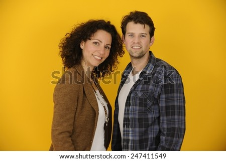 Portrait of couple or partners on yellow background - stock photo