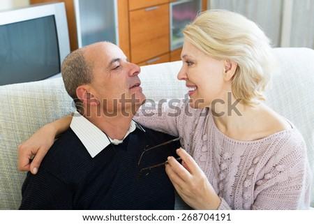 Portrait of couple positive pensioners relaxed at sofa on holiday - stock photo