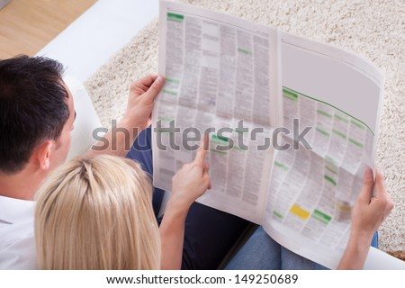 Portrait Of Couple Reading Newspaper Together At Home - stock photo