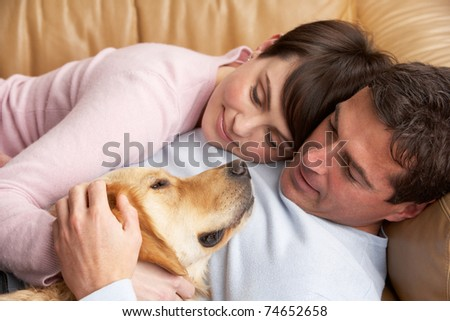 Portrait Of Couple Relaxing On Sofa With Pet Dog At Home - stock photo