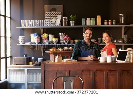 Portrait Of Couple Running Coffee Shop Behind Counter - stock photo