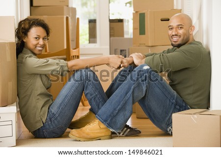 Portrait of couple sitting in new house - stock photo