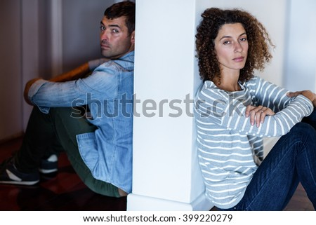 Portrait of couple sitting on opposite sides of the wall and feeling sad - stock photo