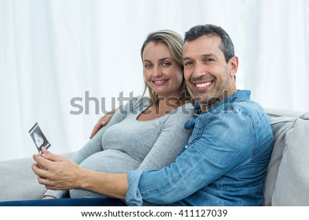 Portrait of couple sitting on sofa and looking at ultrasound scan - stock photo