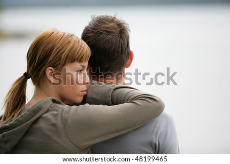 Portrait of couple standing by a lake - stock photo