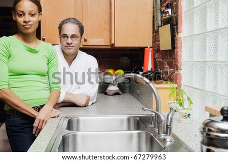 Portrait of couple standing in kitchen - stock photo