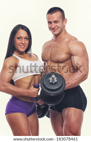Portrait of couple with dumbbells posing in gym - stock photo