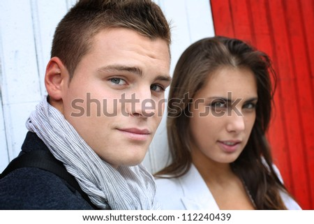 Portrait of couple with serious look standing on sidewalk - stock photo