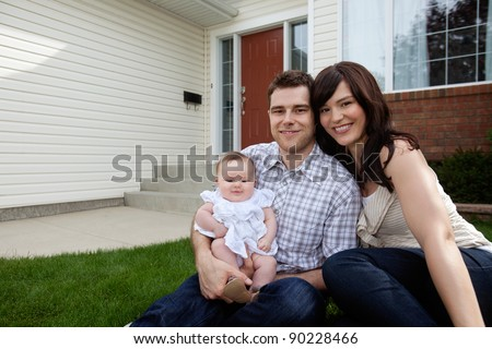 Portrait of couple with their adorable daughter sitting in front of house - stock photo