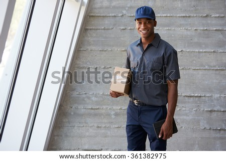 Portrait Of Courier Collecting Package From Office - stock photo
