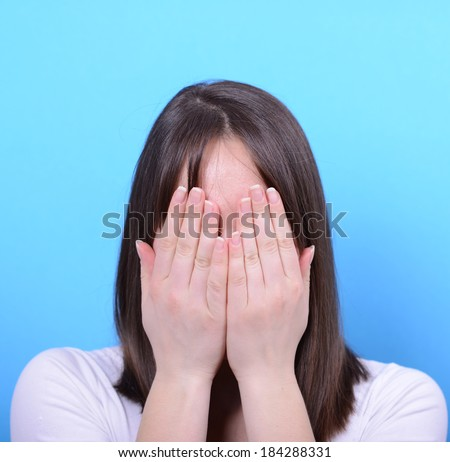 Portrait of covering her face with hands against blue background - stock photo