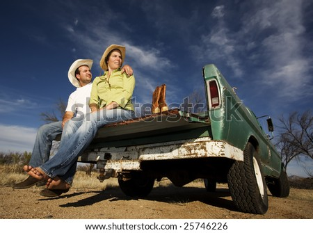 Portrait of Cowboy and woman on pickup truck bed - stock photo