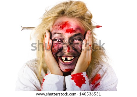 Portrait of crazy blood covered female zombie smiling with nail piercing through head, white background