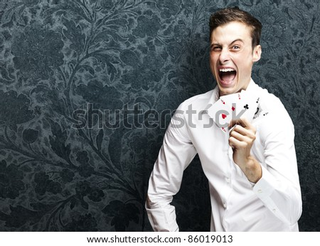 portrait of crazy man showing poker cards against a vintage background - stock photo