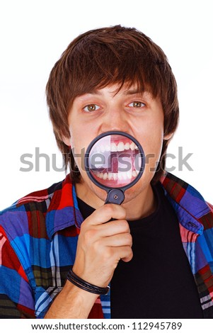 Portrait of crazy student posing in studio with magnifier