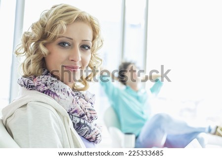 Portrait of creative businesswoman at lobby with colleague relaxing in background - stock photo