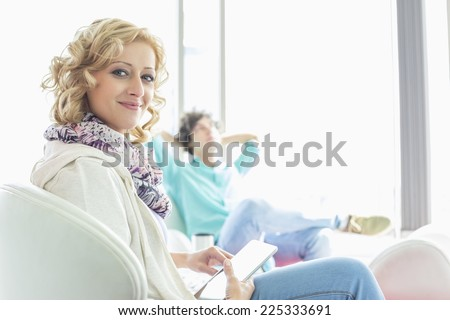 Portrait of creative businesswoman holding digital tablet at lobby with colleague relaxing in background - stock photo