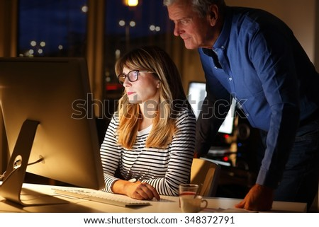Portrait of creative team sitting at office and working late night. Professional woman sitting in front of computer while managing director standing next to her and consult in front of monitor.  - stock photo