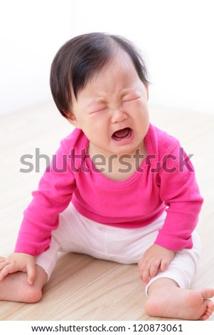 portrait of crying baby girl on living room at home, asian child - stock photo