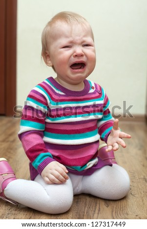 Portrait of crying baby girl sitting on the floor in pink dress - stock photo