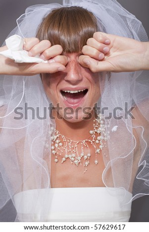 portrait of crying bride over grey background - stock photo