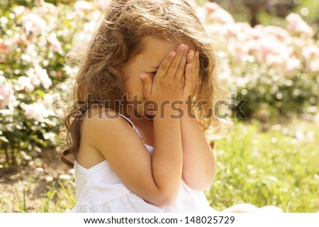 portrait of crying girl with hands on her face - stock photo
