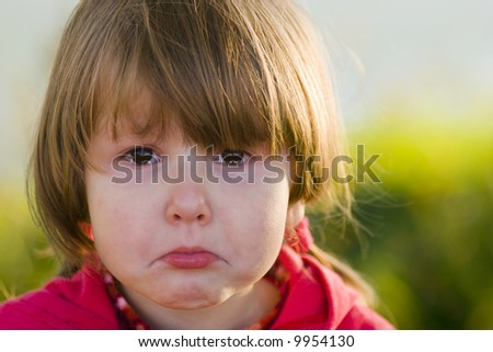 Portrait of crying little girl looking at you, tears filling her eyes, outside - stock photo