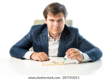 Portrait of cunning businessman putting money in trap as lure - stock photo