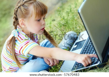 Portrait of curious girl looking at the laptop while touching a key - stock photo